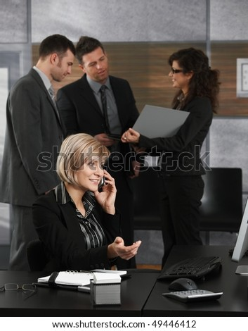 Happy young receptionist receiving phone calls in office smiling. - stock photo