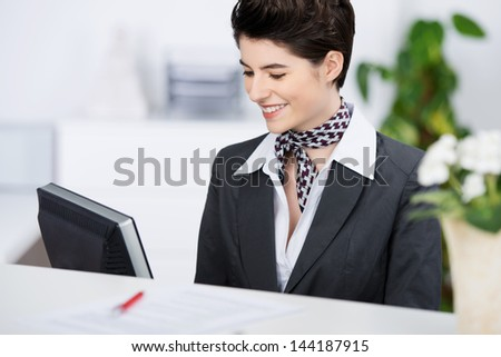Happy young receptionist smiling while using computer at counter