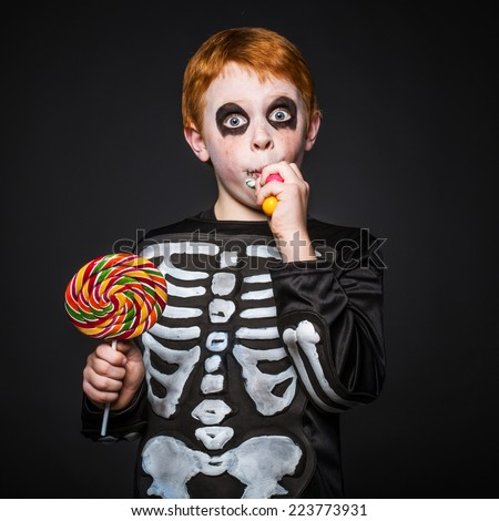 Happy young red hair boy with skeleton costume holding and eating colorful candies. Studio portrait over black background   - stock photo