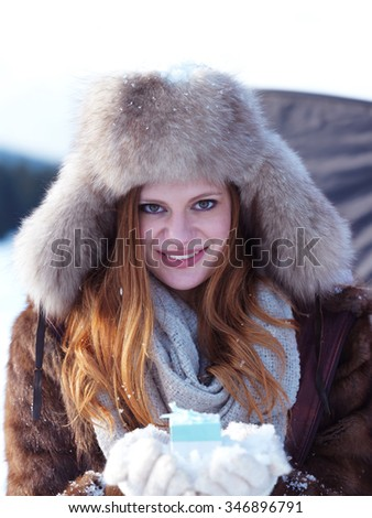 happy young redhair girl  with gift and snow in  hands. Christmas and winter shopping concept, forest in background