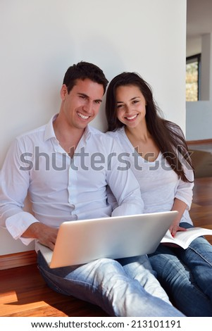 happy young relaxed  couple working on laptop computer at modern home indoor - stock photo