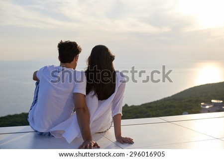 happy young romantic couple have fun relax smile at modern home outdoor terace balcony - stock photo
