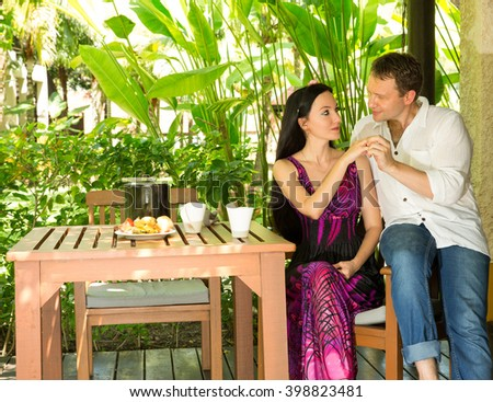 Happy young romantic couple sitting at a table and have lunch at an outdoor.  Love story and people's attitudes. Beautiful marriage concept.  - stock photo