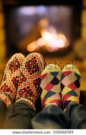 happy Young romantic couple sitting on sofa in front of fireplace at winter season in home - stock photo