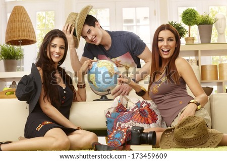 Happy young roommates planning summer holiday, having globe, smiling. - stock photo