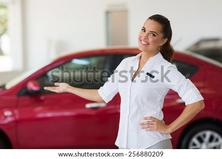 happy young saleswoman welcoming gesture in car showroom - stock photo