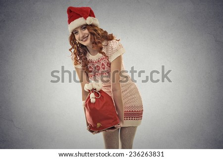 Happy young santa helper girl carrying big red christmas sack full of gifts isolated on grey wall background. Holiday season shopping concept. Positive face expression, emotion - stock photo