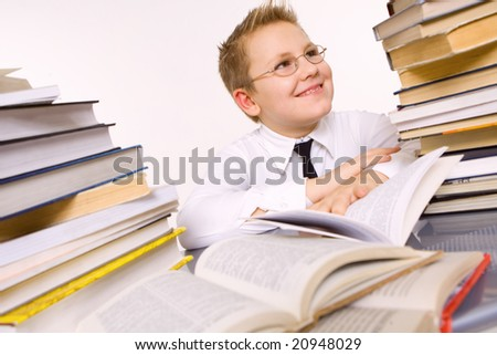 Happy young school boy surrounded by books