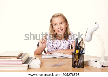 happy young school girl sitting at the table with a ruler and draw a line in the booklet/happy young school girl - stock photo