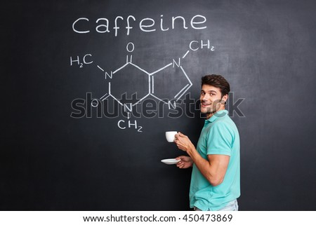 Happy young scientist standing over chemical structure of caffeine molecule drawn on chalkboard background and drinking coffee