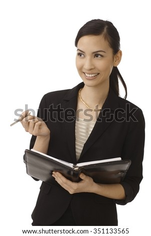 Happy young secretary making notes to personal organizer, smiling, looking away. - stock photo