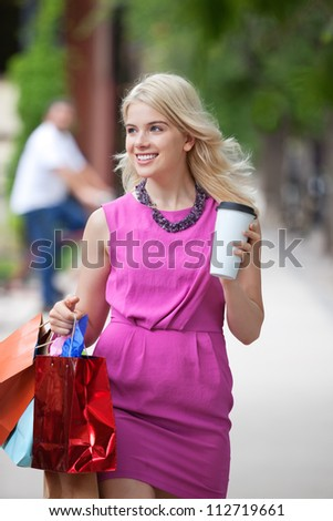 Happy young shopaholic woman with bags and disposable coffee cup walking on sidewalk - stock photo