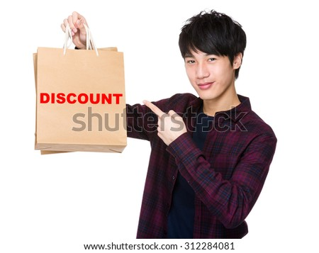 Happy young shopper with finger point to paper bag for showing a word discount