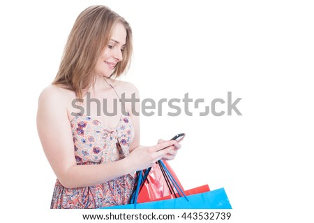 Happy young shopper with gift bags texting on cellphone and doing shopping isolated on white with copy space area