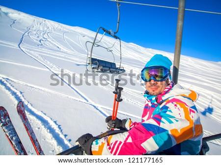 Happy young skier men on a ski-lift, Tirol, Austria - stock photo