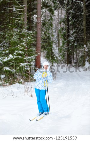Happy young skier with ski poles in hands up in winter forest - stock photo