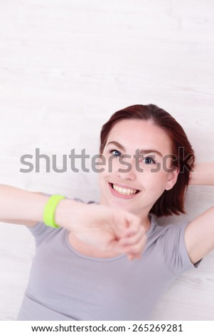 Happy young smile woman look smart watch and relax lying on the wood floor, caucasian beauty - stock photo
