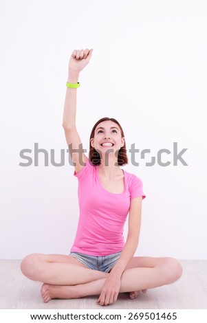 Happy young smile woman look smart watch and sit on the floor with white wall background, great for your design or text, caucasian beauty - stock photo