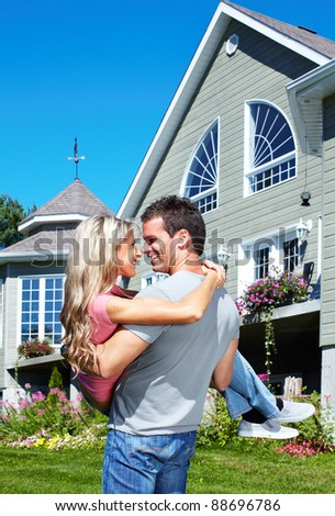 Happy young smiling couple near new home. - stock photo