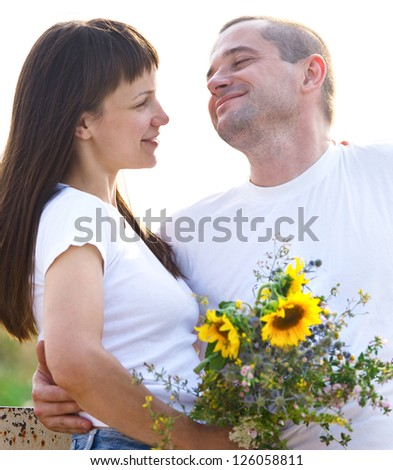 Happy young smiling couple with flowers outdoors