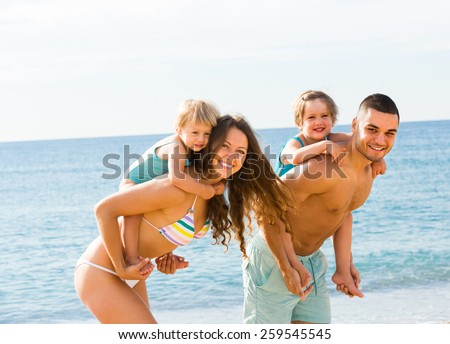Happy young smiling family of four in vacation at sea shore - stock photo