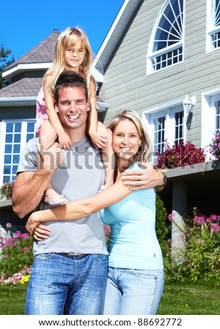 Happy young smiling family with children near new home. - stock photo