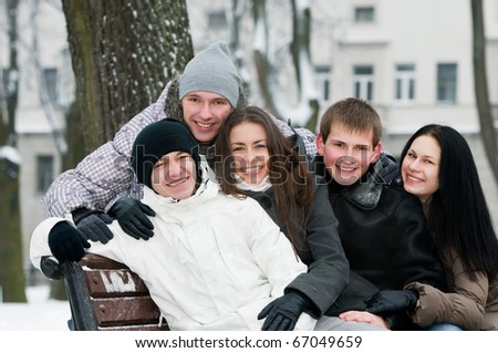 happy young smiling people sitting on a bench in warm clothing at winter outdoors - stock photo