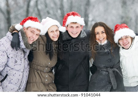 happy young smiling student people group in xmas red hat at cold winter outdoors - stock photo