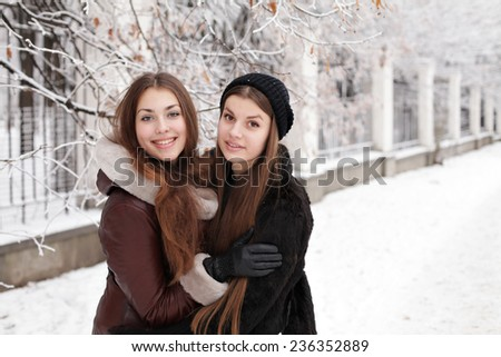Happy young smiling woman hugging in warm clothing at winter outdoors. Portrait of two pretty girls in winter park having fun - stock photo