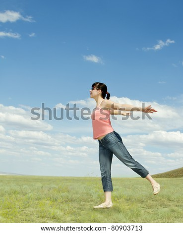Happy young smiling woman in the field enjoy sun - stock photo