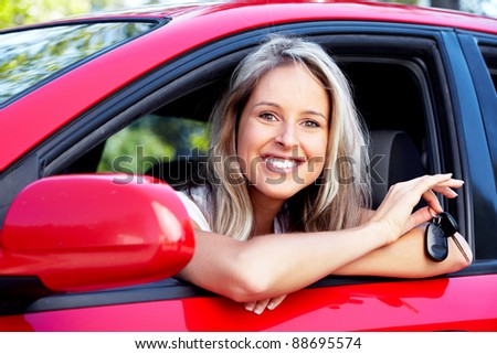 Happy young smiling woman with a car key. New automobile.