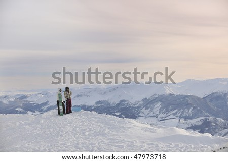 happy young snowboarder couple relax at top of mountain at beautiful sunny winter day