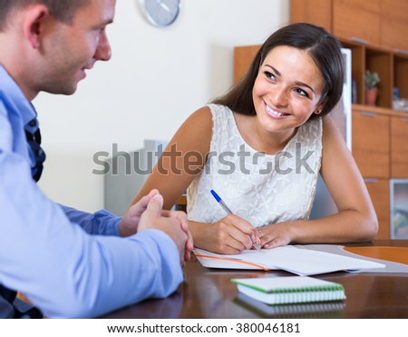 Happy young spanish woman and man with financial documents in agency - stock photo