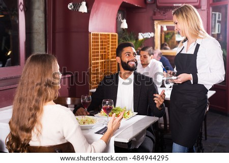 Happy young spouses having date in middle class restaurant. Focus on blonde girl