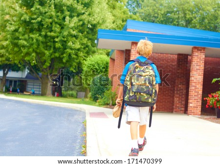 Happy young student going back to school carrying backpack. Cheerful school boy walking  to school building confidently. Color Image, copy space. - stock photo