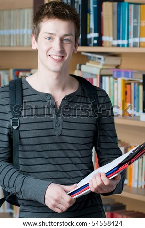 Happy young student holding books in a college library - stock photo