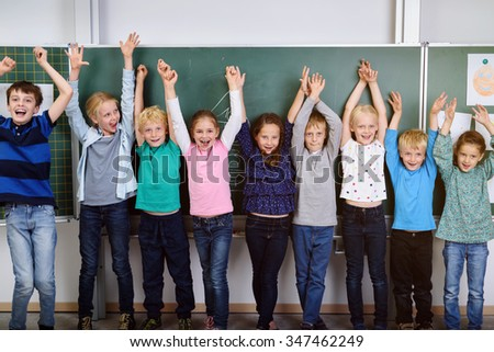 Happy Young Student Raising their Arms Together While Standing Against the Chalkboard Inside the Classroom. - stock photo