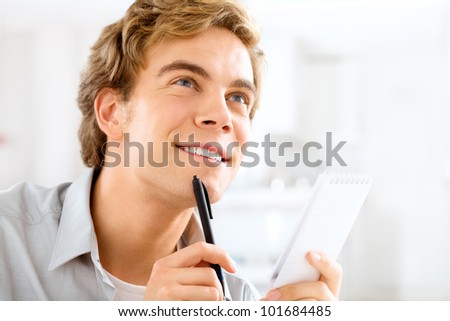 Happy young student studying at home holding pen - stock photo