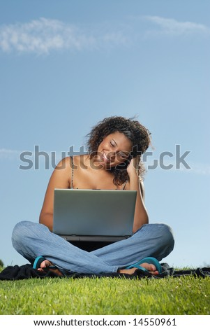 Happy young student working on her laptio outside - stock photo