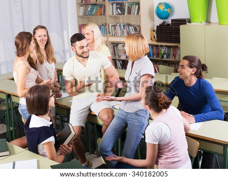 Happy young students during break in classroom interior - stock photo