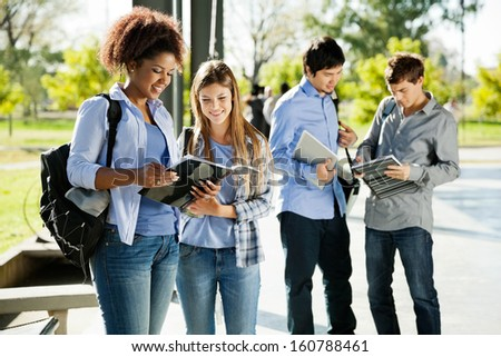Happy young students reading books in university campus - stock photo