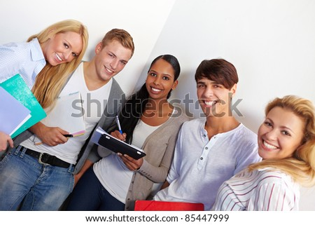 Happy young students smiling in school hall - stock photo