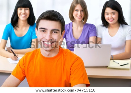 Happy young students studying together in a college - stock photo