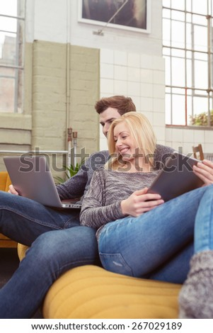 Happy Young Sweet Couple in Casual Outfits Resting at the Couch in the Living Area While Watching a Movie at the Laptop Computer. - stock photo