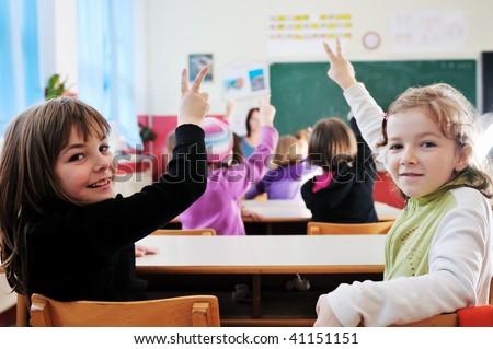 happy young teacher woman at elementary school teaching and giving lessons to group of young smart children - stock photo