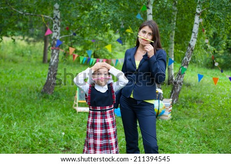 Happy young teacher woman mother and schoolgirl wearing uniform outdoors holding pencils as mustache - stock photo