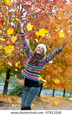 happy young teen girl in autumn scenery throwing leaves