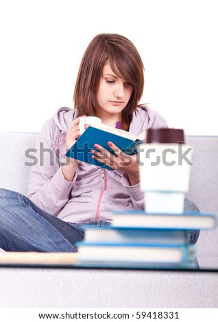 happy young teen reading a book while drinking coffee
