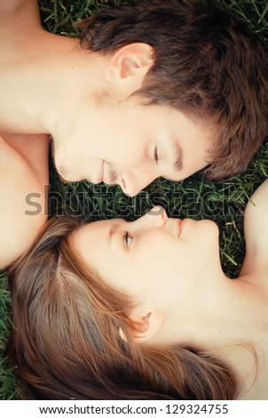 Happy young teenage couple man and woman in love lying on green grass head to head  closeup portrait - stock photo