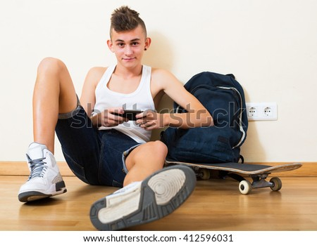 Happy young teenager burying in mobile phone and social networking indoors - stock photo